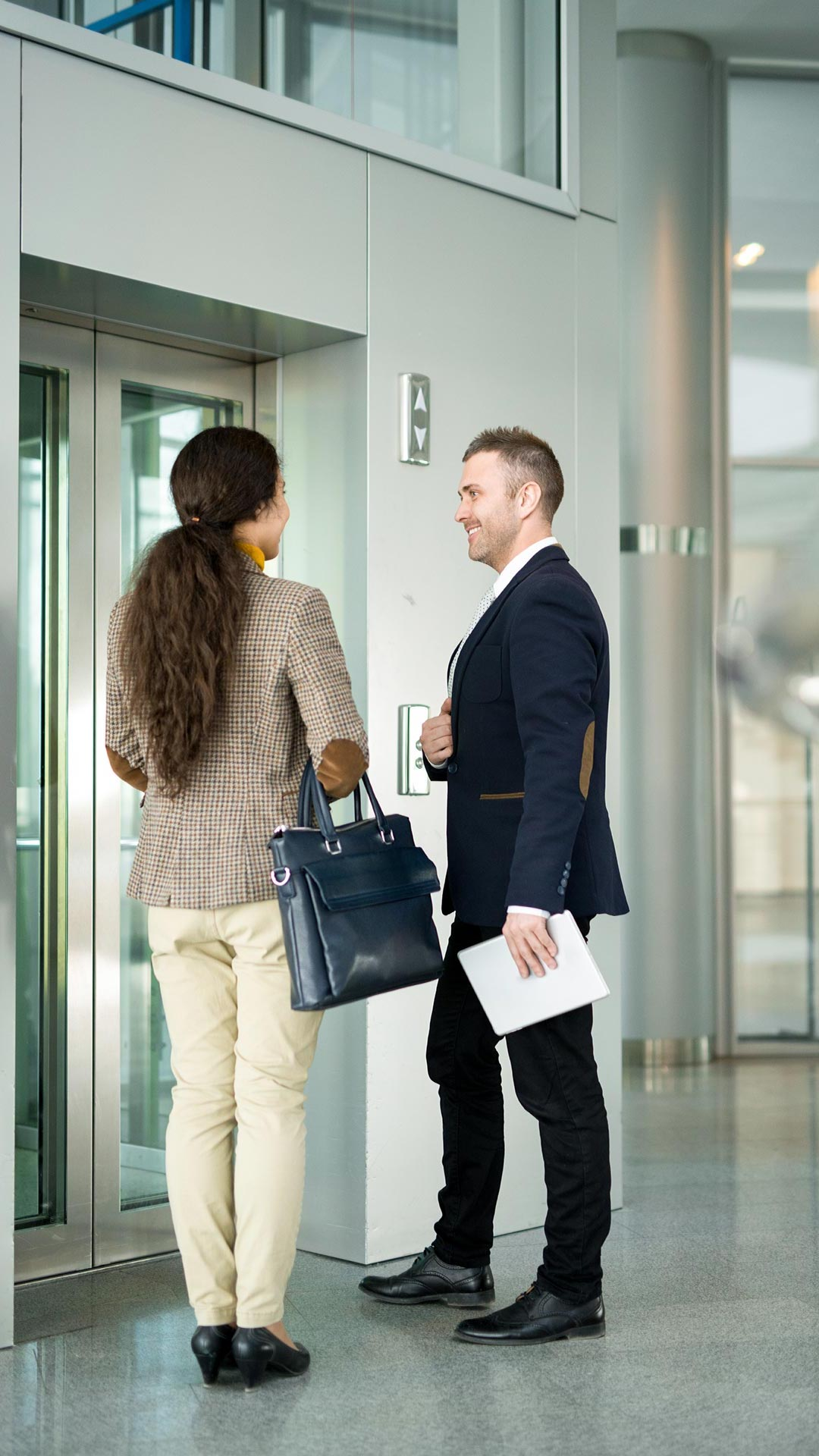 Two people waiting for elevator doors